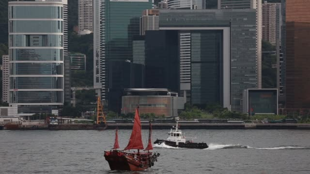 Wide view of skyscrapers and the Hong Kong island skyline as a junk sails in the foreground in Hong Kong China on Thursday July 4 Wide shot a junk...