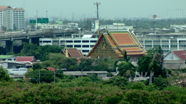 wide view of the roof of a wat or temple located in a garden set against an industrial estate and motorway flyover. - theravada stock videos & royalty-free footage