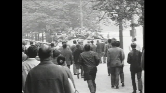 wide view of wenceslas square full of people during the soviet invasion of czechoslovakia; man holding up a flag walking down the street toward the... - prague stock videos & royalty-free footage