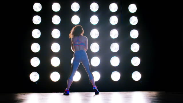 wide view young woman dances with back to camera in front of lights 4k - vesper stock stock videos & royalty-free footage