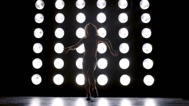 wide view young woman in gym clothes dancing in front of wall of lights 4k - vesper stock stock videos & royalty-free footage