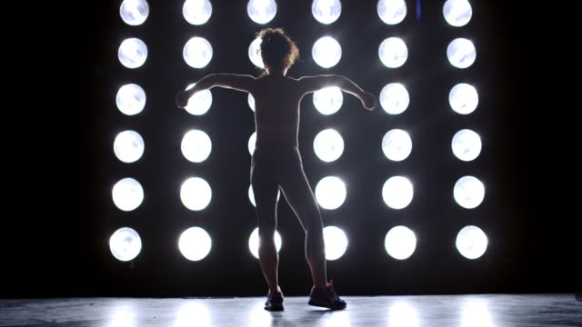 wide view young woman in gym clothes poses in front of wall of lights 4k - vesper stock stock videos & royalty-free footage