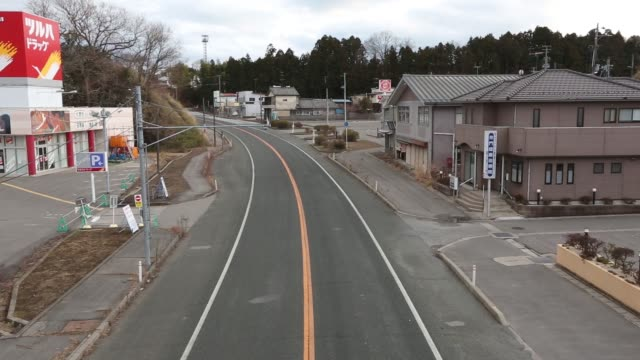 wide views of houses and stores along the main street of the nuclear exclusion zone in namie fukushima prefecture japan on sunday feb 14 traffic... - evacuation stock videos & royalty-free footage