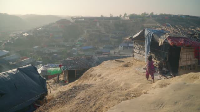 Wide vista of Kutupalong refugee camp in Bangladesh at sunset A small girl walks over to an old injured man sitting in the doorway of his home...