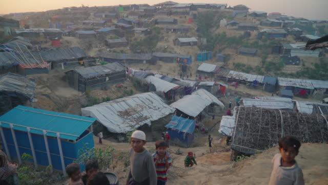 Wide vista of Kutupalong refugee camp in Bangladesh at sunset In the bottom of frame children run and look at the camera Fleeing persecution by the...