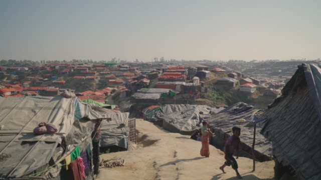 Wide vista of Kutupalong refugee camp in Bangladesh children walk towards the camera up the walkway Fleeing persecution by the Myanmar government and...