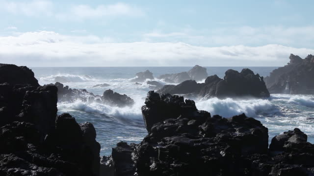 Wide, waves crash on rocky coast