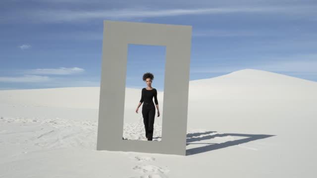 wide, woman in black walks through doorframe in desert - rechteck stock-videos und b-roll-filmmaterial