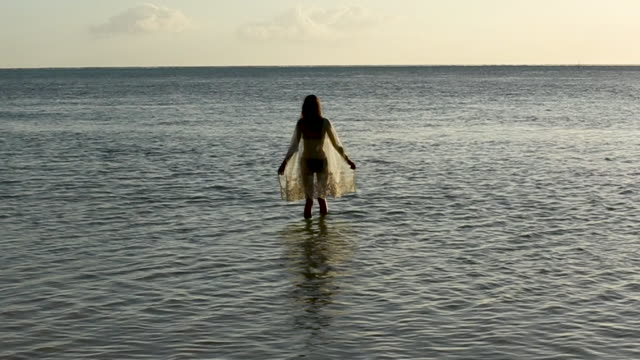 wide, woman wades in tahiti water at sunset - french polynesia stock videos & royalty-free footage