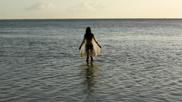 wide, woman wades in tahiti water at sunset - tahiti stock videos & royalty-free footage