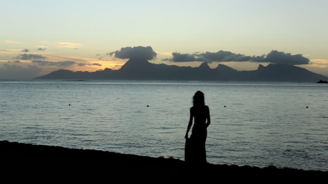 wide, woman walks along tahiti beach at sunset - tahiti stock videos & royalty-free footage
