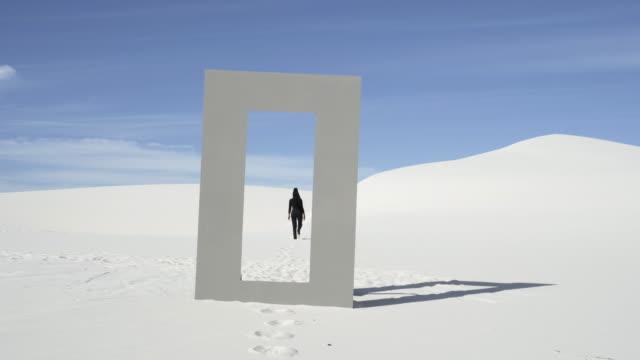 stockvideo's en b-roll-footage met wide, woman walks away from doorframe in desert - sunny