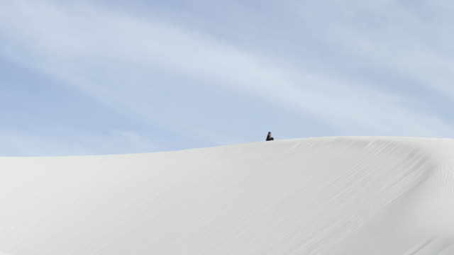 wide, woman walks over sand dunes in desert - wide stock-videos und b-roll-filmmaterial