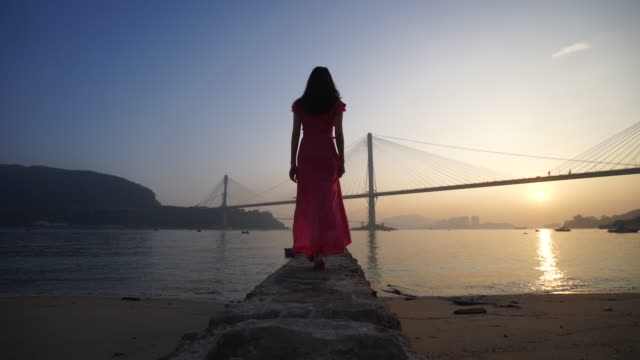 Wide, woman watches sunset over bridge in China