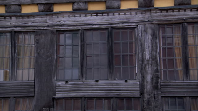 wide wooden beams frame the windows of a medieval cottage in lavenham. available in hd. - lavenham stock-videos und b-roll-filmmaterial