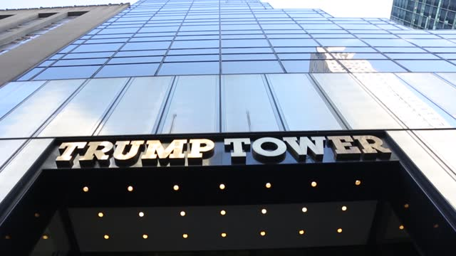wide-angle view tilt shot towards the skyline of the main entrance with a hanging us flag, the inscription trump tower in new york city in the usa.... - new york stato video stock e b–roll