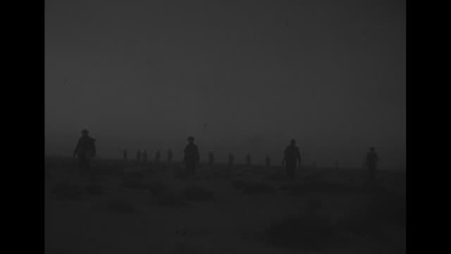 LS widely scattered British soldiers advance across desert to take Tobruk Libya / MS British soldiers cross desert toward camera / PANLEFT high angle...