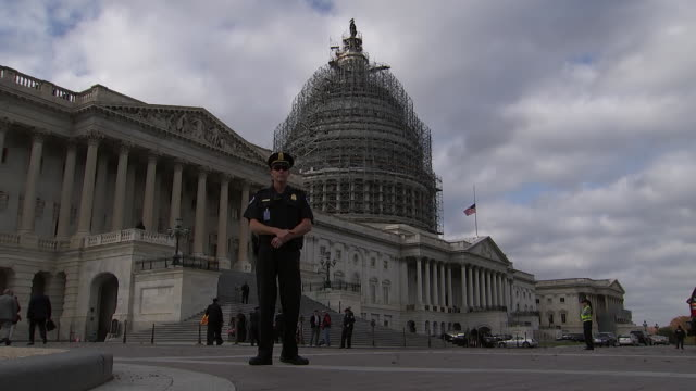vídeos y material grabado en eventos de stock de wide-shot low-angle of policeman on patrol in area in front of washington dc capitol building. the capitol is under construction with scaffolding, an... - music or celebrities or fashion or film industry or film premiere or youth culture or novelty item or vacations