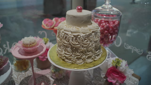 wideshot of a small town bakery display window filled with cakes and goodies. camera dollies forward, ending on a closeup of a beautifully decorated cake. - ornate stock videos & royalty-free footage