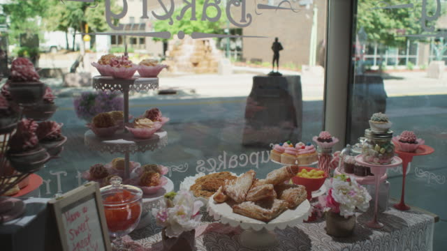 Wideshot of a small town bakery display window filled with pastries, cakes and goodies.