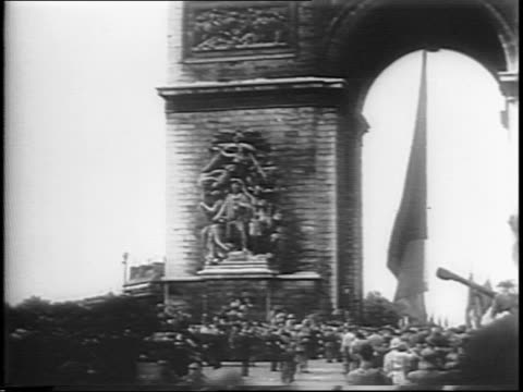 Wideshot of General Charles de Gaulle in parade Arc de Triomphe in background / truck driving through crowd / de Gaulle in procession / crowds of...