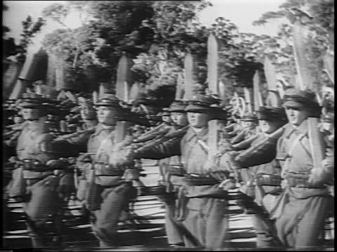 vidéos et rushes de wideshot of presidential box and crowd watching military parade / man with baton directing parade, soldiers marching in background / close-up on... - 1944