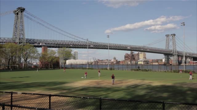 wideshots of the williamsburg bridge as a little league baseball game takes place on a diamond along the east river in manhattan new york - little league stock videos and b-roll footage