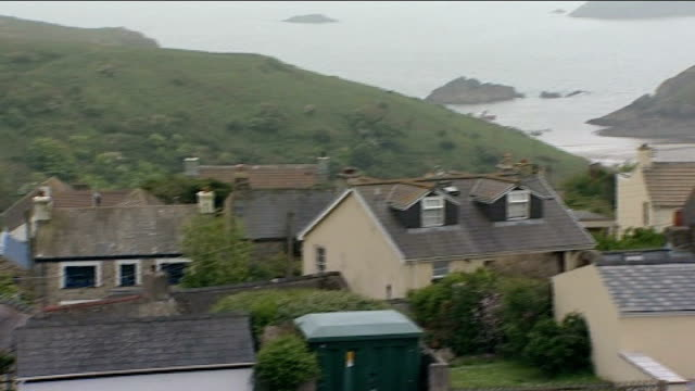 vídeos de stock, filmes e b-roll de widow leaves fortune in her will to villagers as thank you gift wales pembrokeshire solva ext high angle view village and coastline beyond - widow