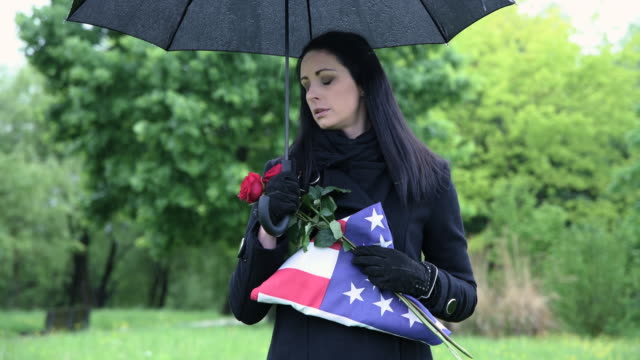 widow of fallen soldier holding americain flag at cemetery - war memorial stock videos & royalty-free footage