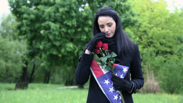 widow of fallen soldier holding americain flag at cemetery - us memorial day stock videos & royalty-free footage