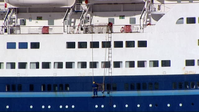 widow of man killed by wave on cruise ship criticises bad maintenance; england: essex: tilbury: ext various of worker repairing windows on side of... - witwe stock-videos und b-roll-filmmaterial