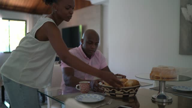 wife bringing basket with bread to husband for breakfast at home - husband stock videos & royalty-free footage