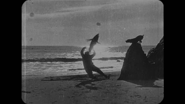 vídeos de stock e filmes b-roll de 1916 wife (mabel normand) calls to husband (fatty arbuckle) who is fishing in the ocean - captura de peixe