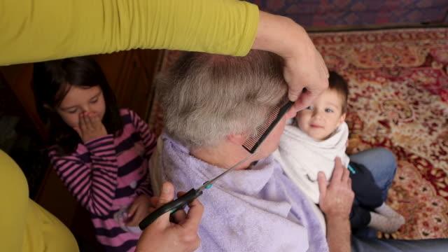 stockvideo's en b-roll-footage met vrouw die het haar van haar echtgenoot thuis snijdt - in een handdoek gewikkeld