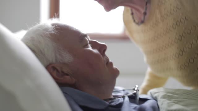 vídeos de stock, filmes e b-roll de wife gives ill husband kiss on forehead - esposa