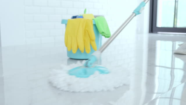 wife housekeeping and cleaning concept, happy young woman in blue rubber gloves wiping dust using mop while cleaning on floor at home - pavimento video stock e b–roll