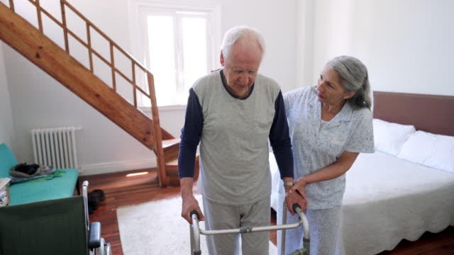 wife is helping her husband with mobility walker at home - walking frame stock videos & royalty-free footage