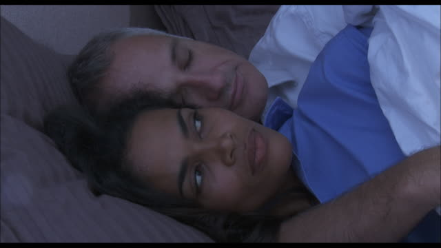 a wife looks at her husband as they snuggle in bed together. - husband stock videos & royalty-free footage