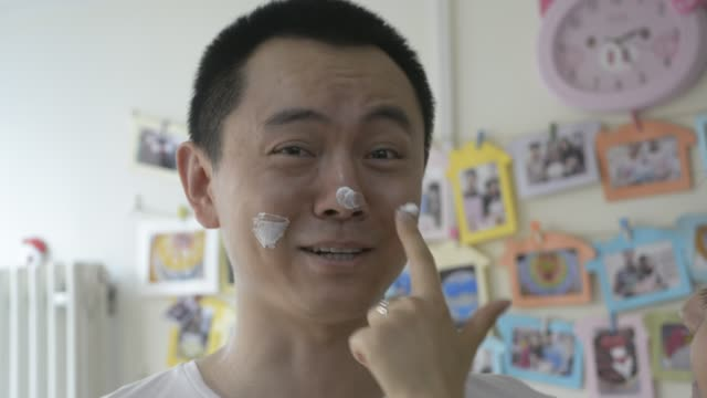 wife put cream on husband face during cake making