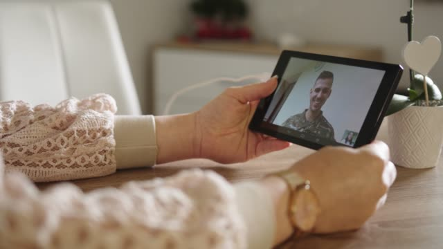 vídeos de stock e filmes b-roll de wife talking to her army husband using a tablet - oficial posto militar