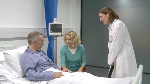vídeos de stock e filmes b-roll de wife visiting husband in hospital, talking to doctor - visita