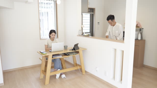 wife working at home office while husband washing dishes in the kitchen - 家事点の映像素材/bロール