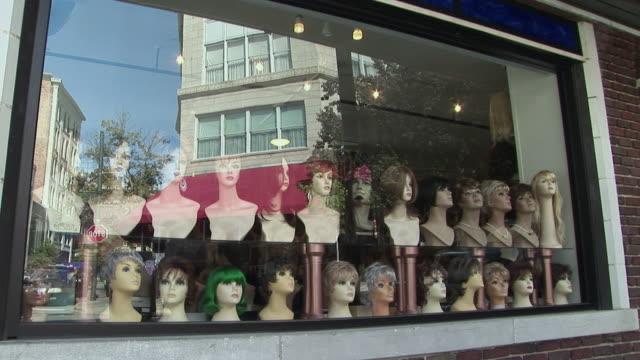 stockvideo's en b-roll-footage met ms, wig shop window reflecting building, asheville, north carolina, usa - pruik
