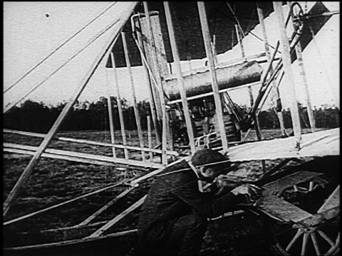 vídeos de stock e filmes b-roll de wilbur wright attaching launching wheel to airplane before / kitty hawk nc - 1903