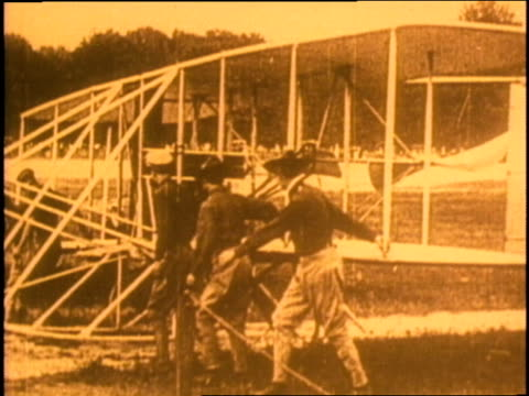 vídeos de stock e filmes b-roll de orville and wilbur wright make preparations to take off in their biplane - 1903