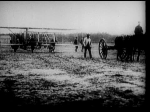 wilbur wright placing wheel under airplane wing, horse towing over field, wilbur talking w/ hart o. berg & unidentified man, brother orville, vs... - brother点の映像素材/bロール