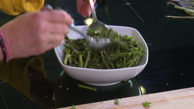wild asparagus salad top view of a woman mixing a vinaigrette into a chopped wild asparagus salad - bowl stock videos & royalty-free footage