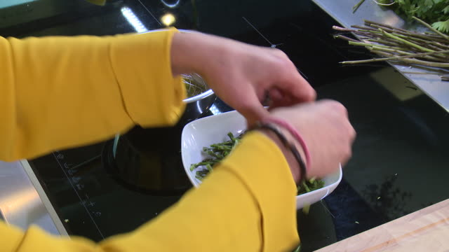 wild asparagus salad top view of a woman pouring a vinaigrette onto chopped wild asparagus - bowl stock videos & royalty-free footage