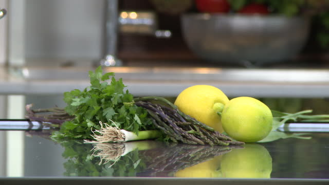 wild asparagus. view of wild asparagus, pasley, green onion and lemons on a kitchen counter. - kitchen worktop stock videos & royalty-free footage