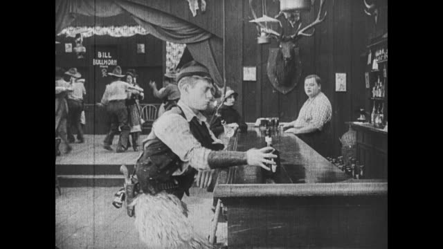 1918 wild bill hiccup returns to the bar and orders drink from bartender (fatty arbuckle), who is chatting with the salvation army woman - ordering stock videos and b-roll footage